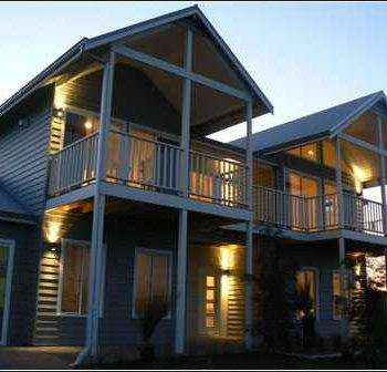 street view of large wooden two story house and dusk with inside lighting.